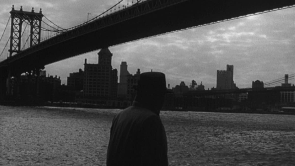Still from Blast of Silence. Frankie Bono walks in front of a NYC bridge, silhouetted by the city skyline.