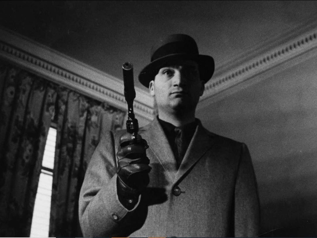 Still from Blast of Silence. Frankie Bono is shot from a low angel by the camera. He is wearing a fedora, trench coat, and holding a pistol with a silencer.