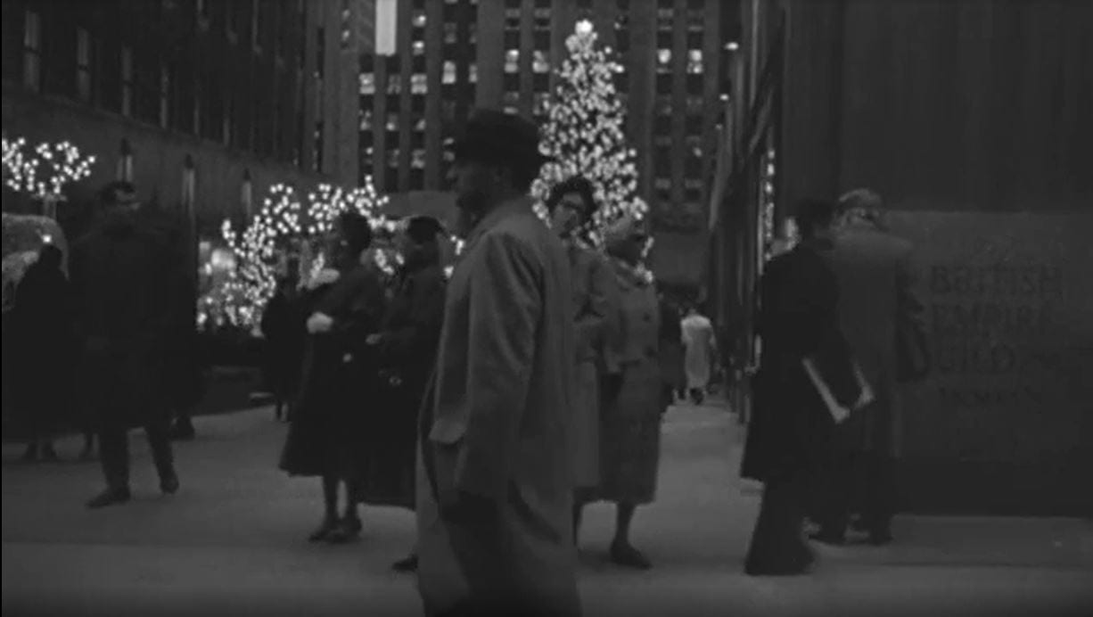 Still from Blast of Silence. Frankie Bono walks past the tree at Rockefeller Center. He is wearing a trench coat and looking very purposefully forward, as if ignoring the tree to his right.