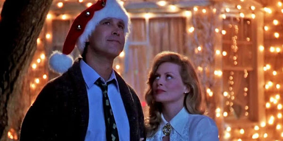Clark and Ellen Griswold in front of their house, with Christmas lights on it, in Christmas Vacation