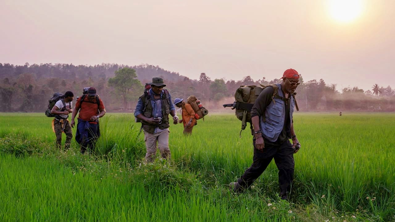 A group of men walk across a green field in Vietnam