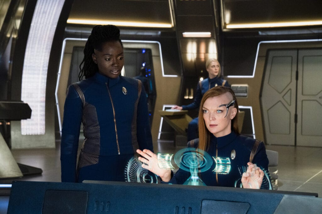 Owosekun (Oyin Oladejo) stands behind Detmer (Emily Coutts) as Detmer works the Discovery control panel