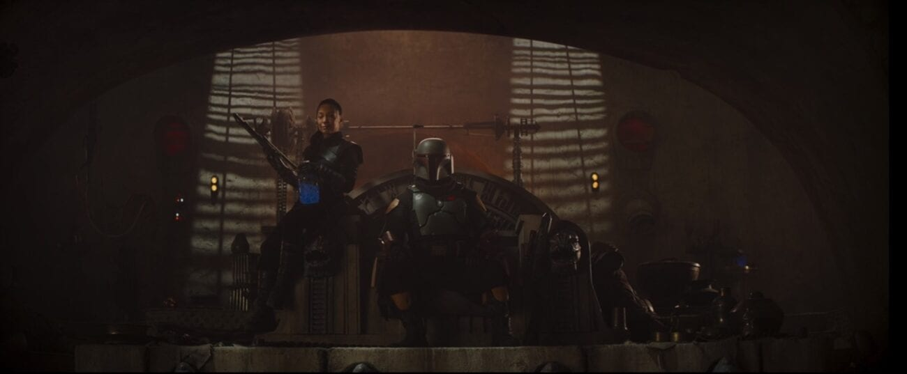 Boba Fett sits on the throne at the old Jabba's palace, with Fennec Shand at his right hand