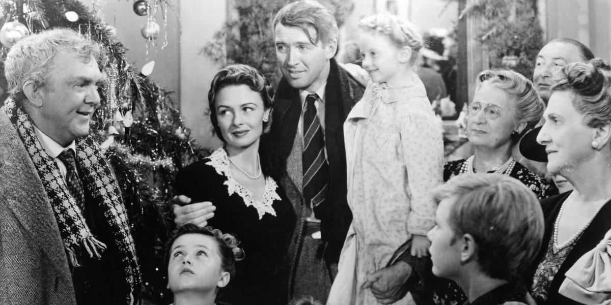 George Bailey surrounded by his friends and family, with a Christmas tree to his left, in black and white photo from It's A Wonderful Life