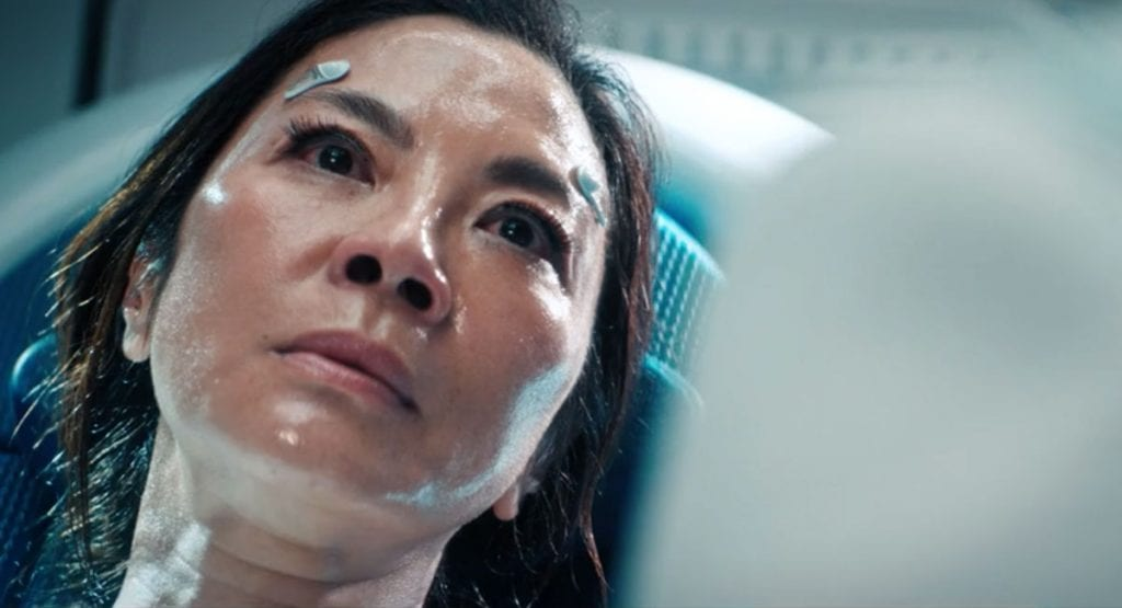 Close up of Georgiou (Michele Yeoh) sweaty and injured lying on a white headrest