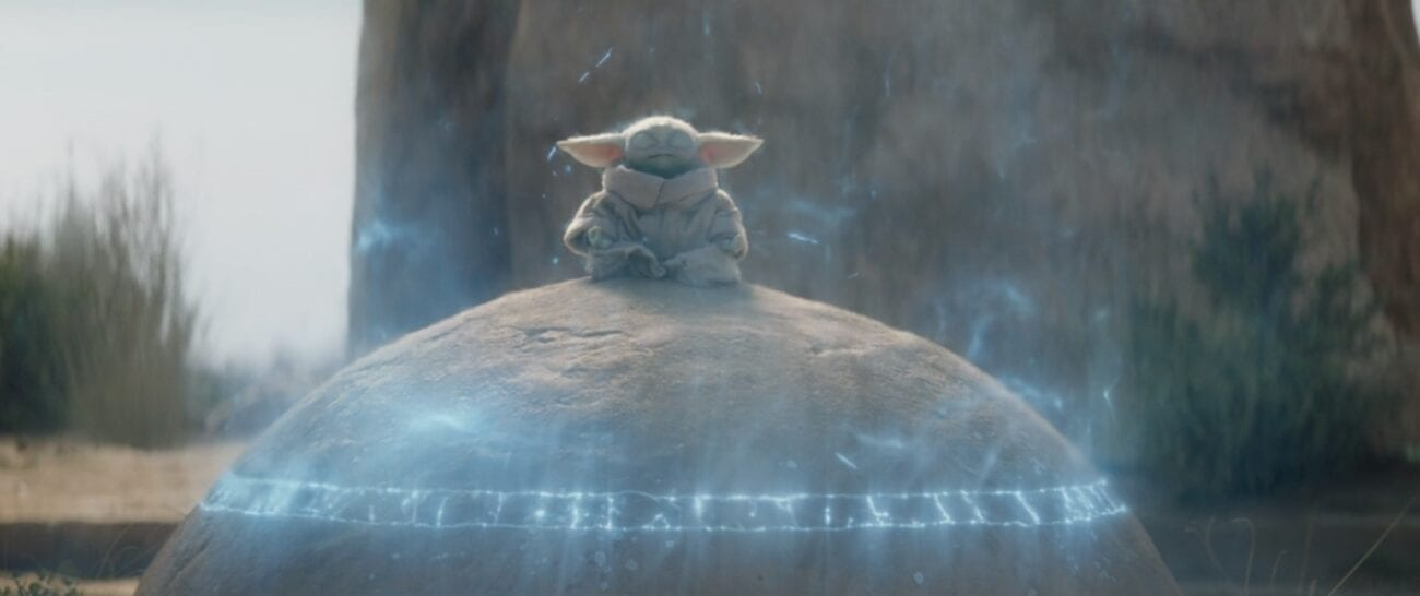 Grogu sitting on the seeing stone while in a Force trance, surrounded by a blue field