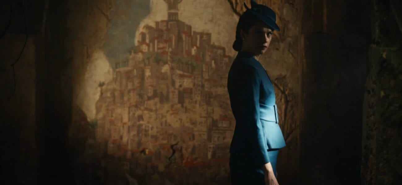His Dark Materials S2E4 - Mrs. Coulter looks right over her shoulder, with a mural of Cittàgazze behind her