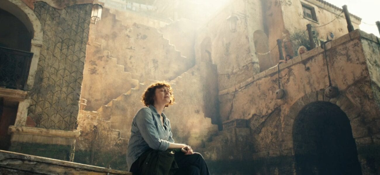 His Dark Materials S2E6 - Mary Malone sits on a stone wall with the backdrop of Cittagazze behind her, sunlight beaming down on her
