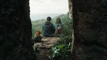 His Dark Materials S2E6 - Pan, Will and Lyra sit at the edge of a rock crevice, looking out over lush green moutainside