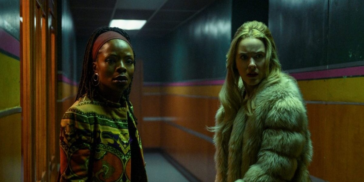 Teri wears a colorful overcoat and Jean wears a fur coat as the look toward the camera in a long hallway