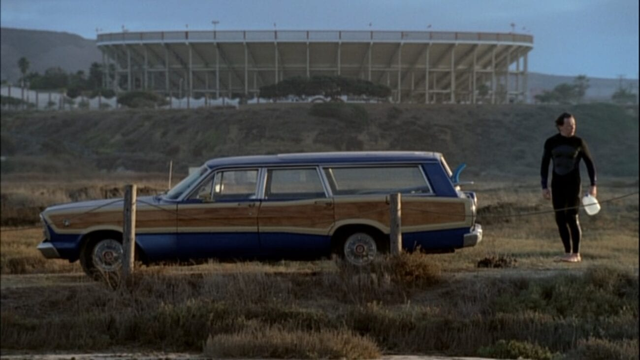 Mitch stands at the rear of his station wagon floating off the ground