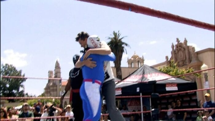 John hugs a luchador in the middle of a wrestling ring