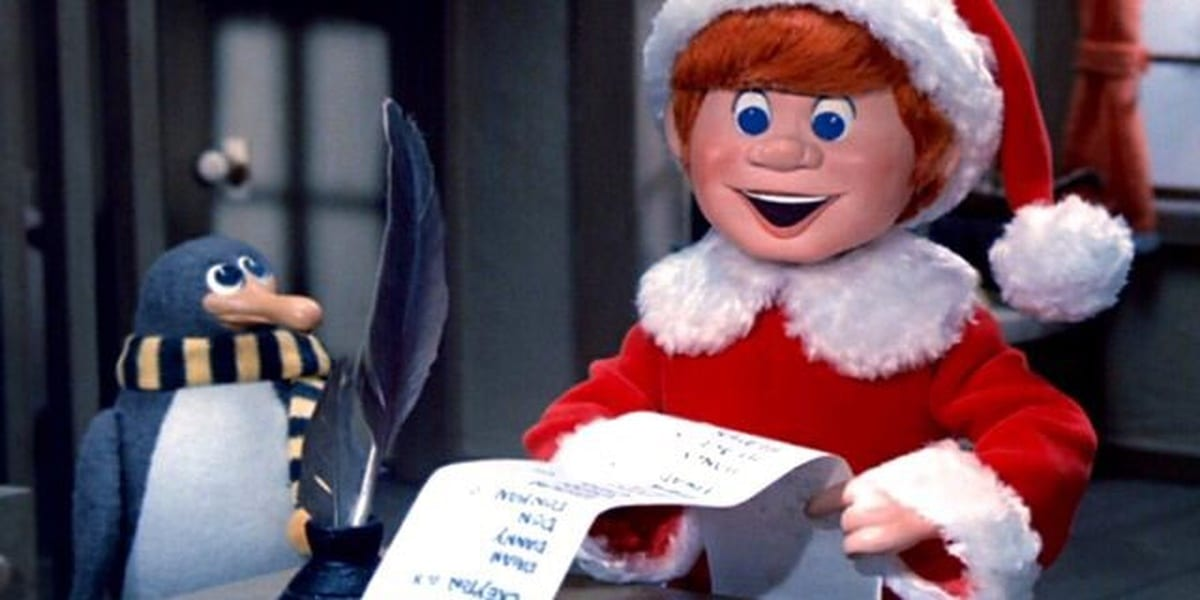 Kris Kringle holding a list, with Topper the penguin, in Santa Claus is Comin to Town