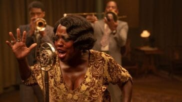 Ma Rainey sings into a recording microphone in front of her band.