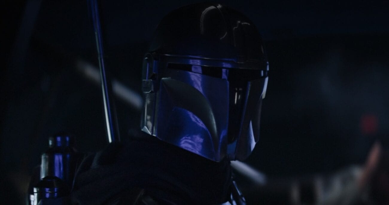 Mando in the cockpit of an Imperial Shuttle, with his armor reflecting blue lights