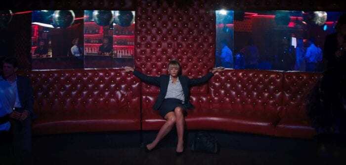 Cassie sits on a club couch provacatively.