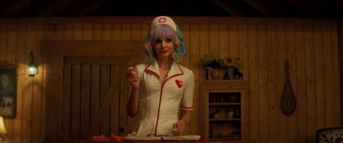 Cassie, dressed as a nurse, brandishes a scalpel.
