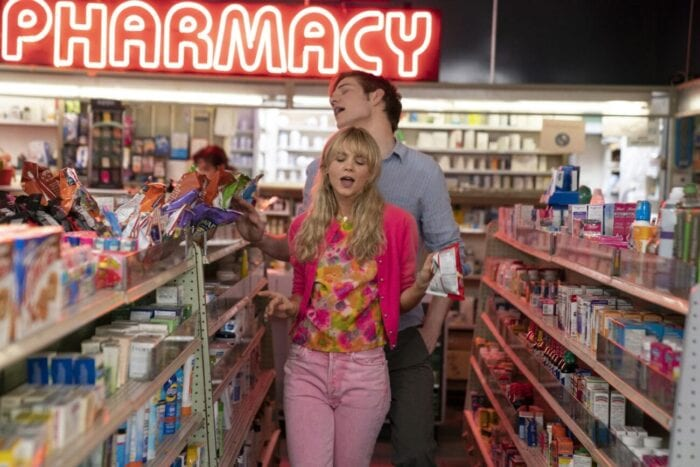 Cassie and Ryan dance and sing in a pharmacy aisle.