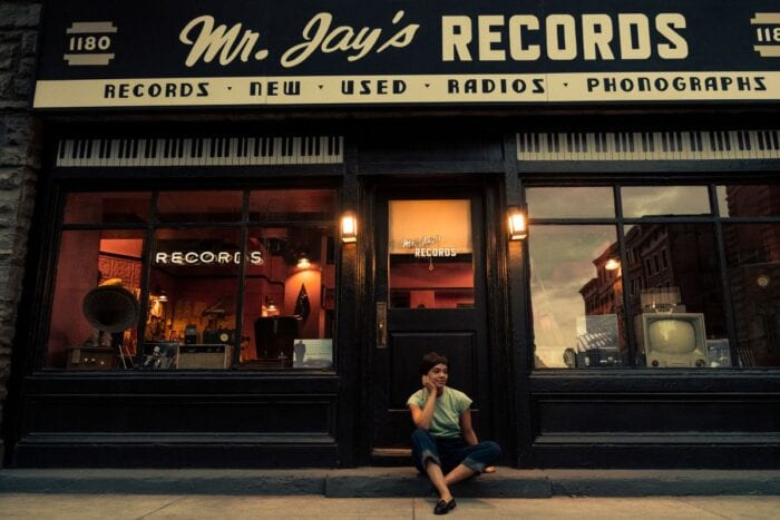 Sylvie sits on the sidewalk outside her father's record store.