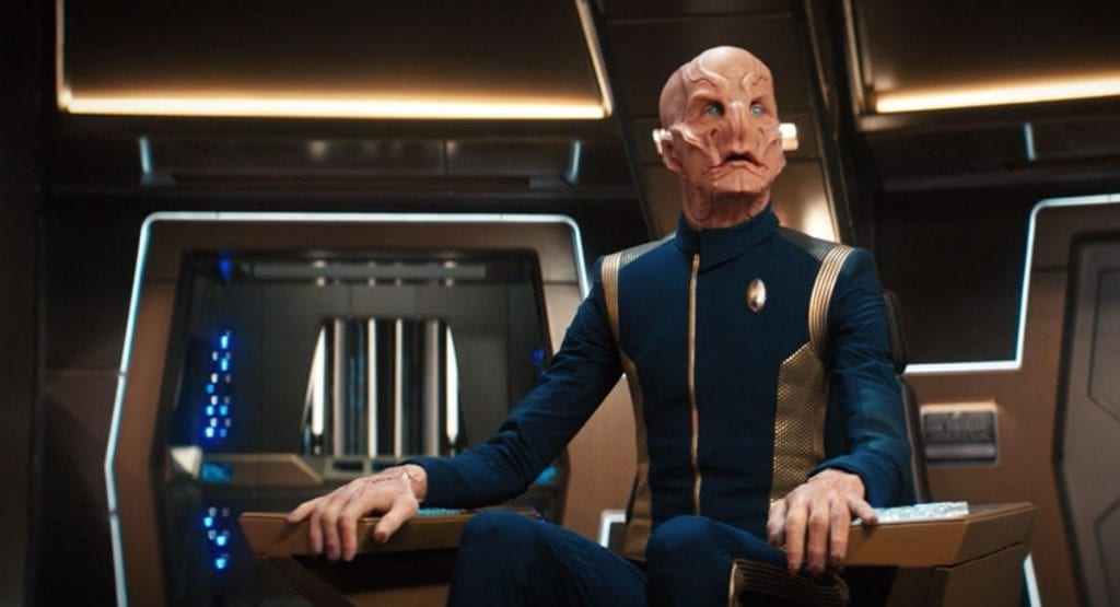 Captain Saru (Doug Jones) sits at the conn on the Discovery bridge looking off to the left