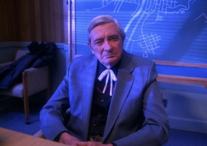 Judge Sternwood sits in the Twin Peaks Sheriff's department conference room, briefly lit by the thunderstorm outside.