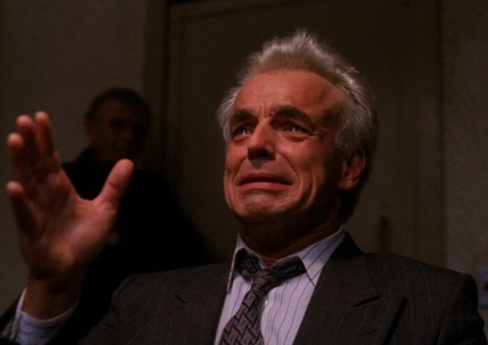 Leland Palmer tearfully confesses his crime to someone off screen, while Doc Hayward watches in the background.