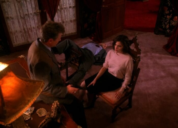 Audrey Horne sits in a chair while a body with a gunshot wound lies on the floor next to her, Jean Renault leans on the desk in front of her holding a gun.