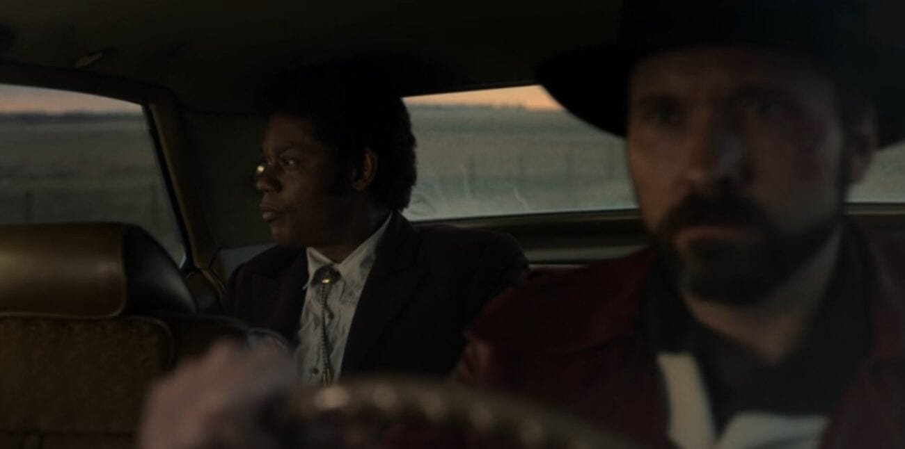 Mike Milligan watches the sunset out of the rear passenger window of a 1970s era car while his driver keeps his eyes forward.