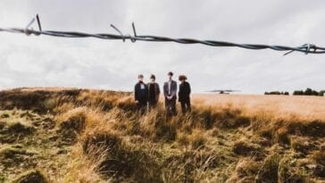 The four band members of The Lounge Society standing in a field