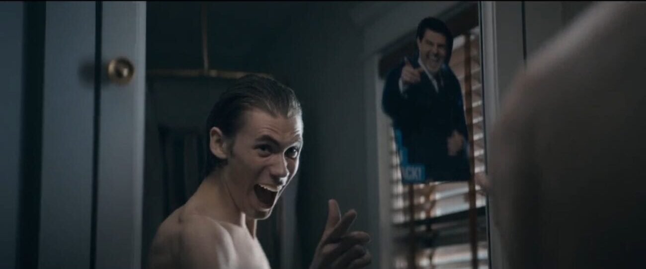 The Stand S1E1 - Harold fakes a smile in the bathroom mirror, imitating a picture of Tom Cruise taped to the mirror