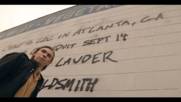 The Stand S1E1 - Harold Lauder stands in front of a message spray painted on the storefront wall