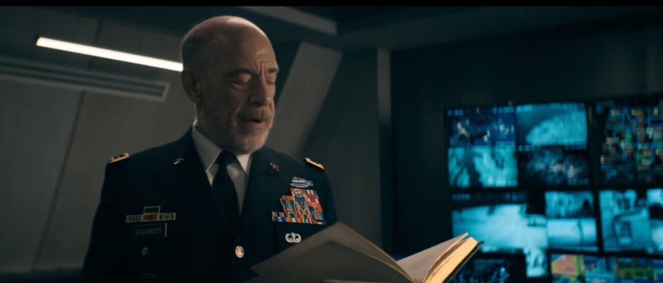 The Stand S1E1 - General Starkey holds a book in his hand and is reading aloud from it