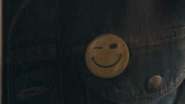 The Stand S1E2 - A smiley face button pinned to a jean jacket winks