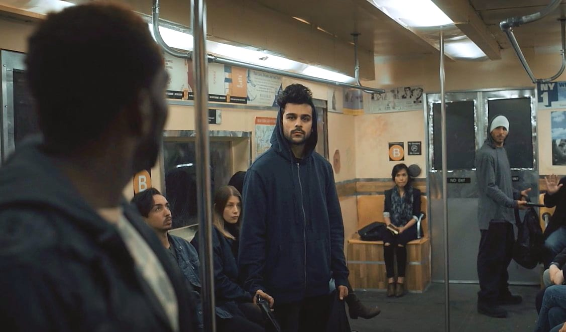 Kevin, Jemar and Waheed stand in a train car full of passengers they are robbing