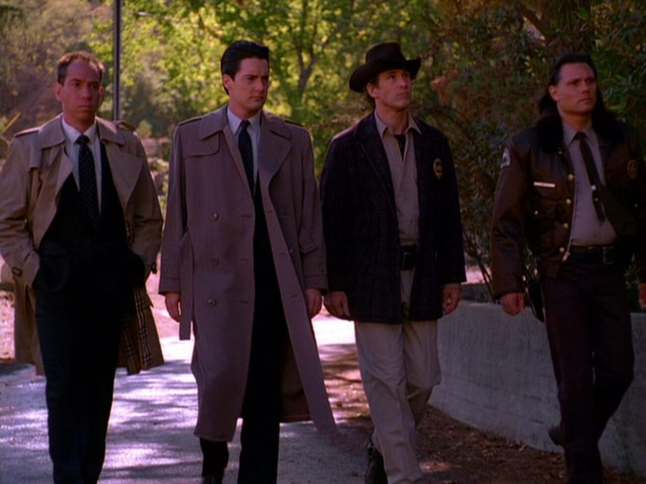 Two FBI agents and two police officers, Albert, Dale, Harry, and Hawk, walk down a sidewalk in a line.