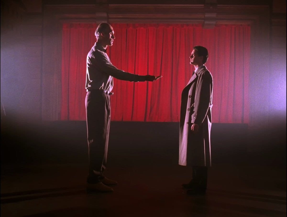 Dale Cooper and The Giant stand facing each other in front of a red curtain and the Giant extends his hand to Cooper.