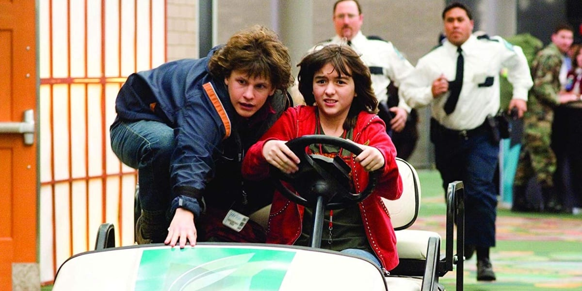 Spencer and Grace in Unaccompanied Minors driving airport car being chased by security guards