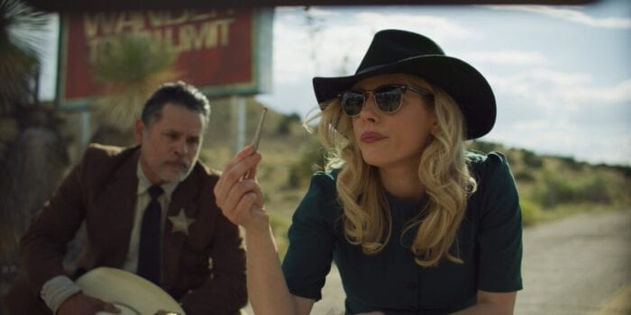 Elsa examines a piece of evidence wearing a hat and sunglasses next to the sheriff.