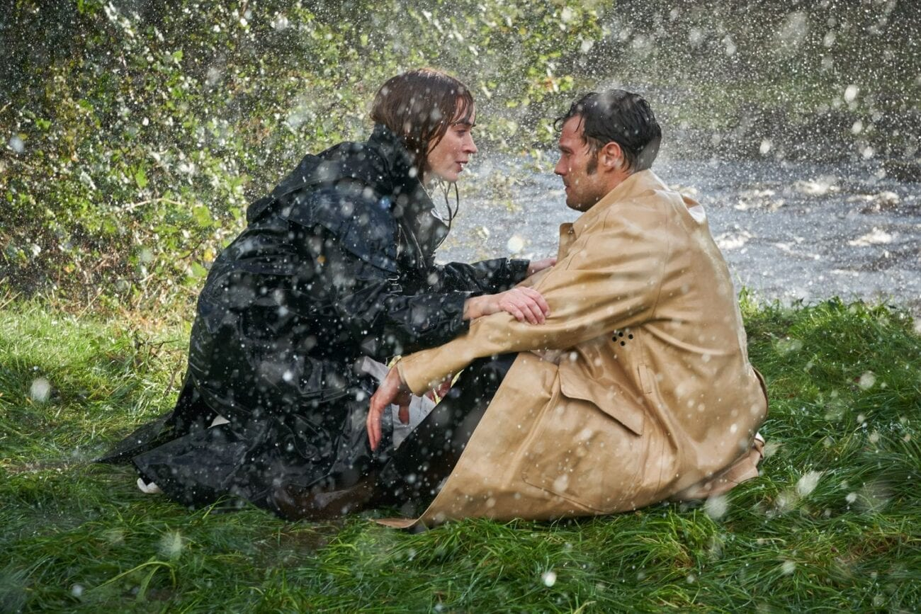 Rosemary and Anthony talk while kneeling and seated in the rain.
