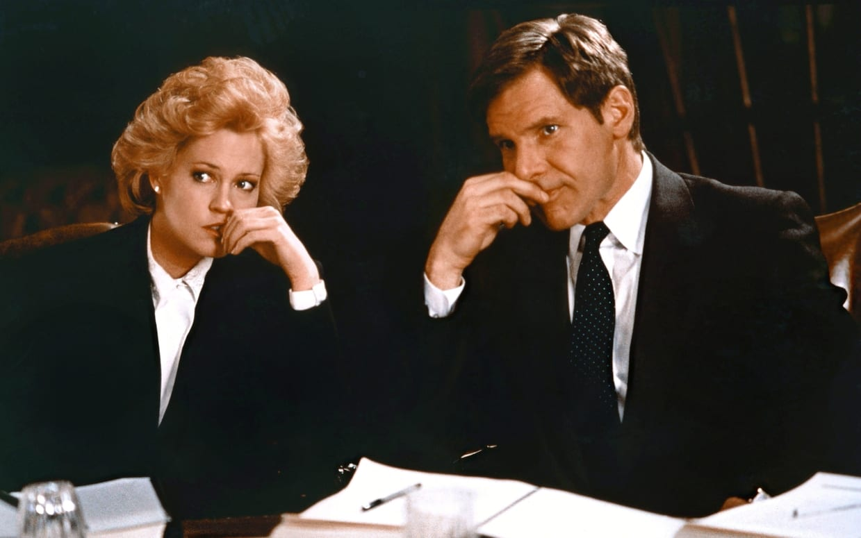 Tess McGill and Jack Trainer sent nervously at a board meeting table