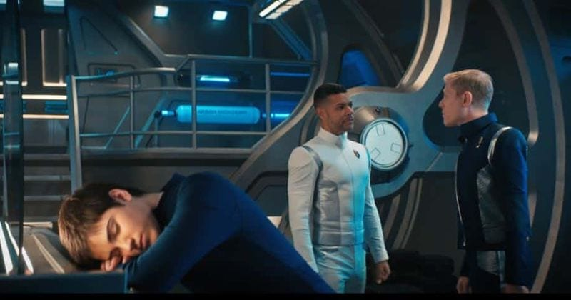 Adira (Blu Del Barrio) rests their head on a console while Culber (Wilson Cruz) and Stamets (Anthony Rapp) discuss them in the background