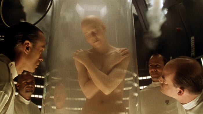 several men in science coats peer into a glass tank containing a naked and bald woman