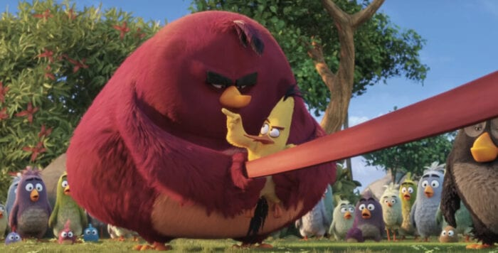 Terence (a very large bird, almost identical to Red but with darker coloring) preparing to launch Chuck (a small, vaguely triangle shaped yellow bird with long black tail and head feathers, a long orange beak and reddish brows) from a slingshot. Chuck is pointing a finger at him as though giving instructions. Terence looks angry.