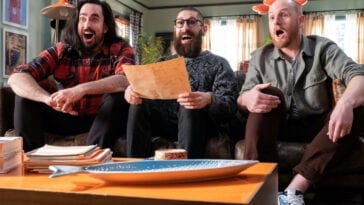 Aunty Donna sit on a couch looking excited