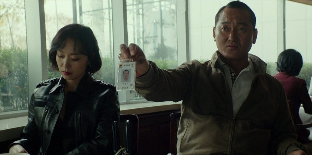 A woman in a leather jacket and a man holding an ID badge sit in a café in Beasts Clawing at Straws.