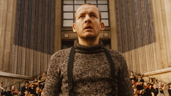 a man stands in front of a large building, behind him a full orchestra plays