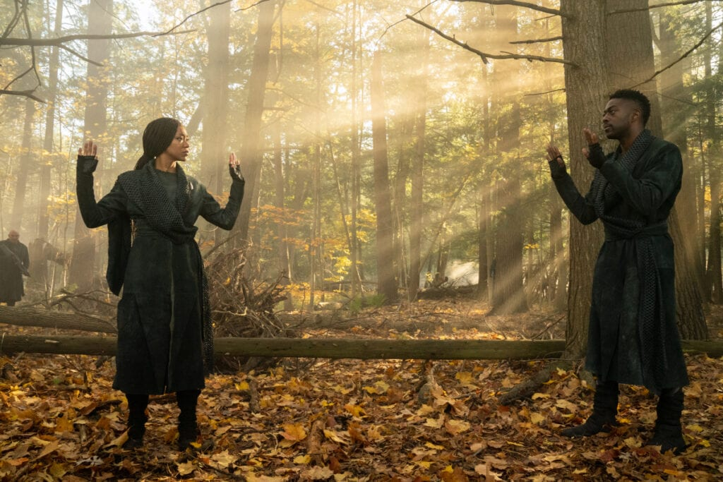 Burnham (Sonequa Martin-Green) and Book (David Ajala) stand in leafy clearing in a forest with their hands raised in the air as a sun shines through the trees