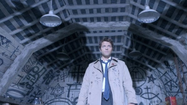Castiel stands in a trenchcoat and tie in front of a wall covered in symbols