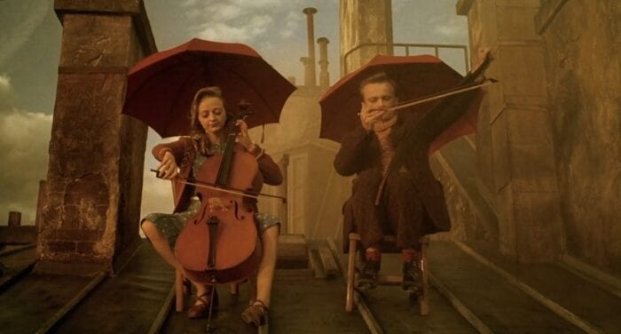 Julie and Louison sit on the rooftop playing instruments. Julie plays the cello while Louison plays a musical saw.