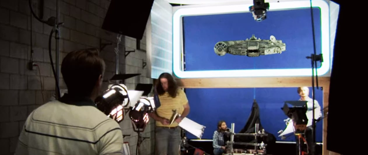 A young Jim Swearingen walks into a studio set where the crew of Star Wars is taking shots of the Millenium Falcon model, cameras and lights are on the model and several 70s figures are in the background
